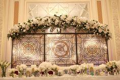 Витражными зонами декорирована зона церемонии, задник за столом молодоженов, вазы, свадебная полиграфия.