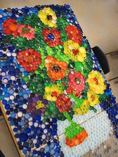 These bottle cap mosaics are amazing, but you must collect a lot of caps first! instead of bottle caps use the flat kinda see through rocks that go in a fish tank