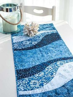 "An easy project to whip up for the holidays! This table runner and place mat pattern is perfect for all those large-scale prints that have been giving you that come-hither look. Quick-to-stitch and super trendy, the finished project makes for a great gift for any special person in your life. You can jazz up the finished look by adding some extra stitches here and there, embellishments, and your favorite fabrics. Finished sizes: Table runner: 15"" x 47"" Place mats: 14"" x 18 1/2"" each"