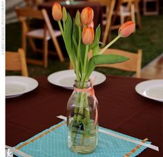 For months prior to the wedding, the bride had asked everyone she knew to drink more milk, and to drink it from glass jars. She then arranged orange tulips, her other favorite flower, in the jars as centerpieces for the tables. She cut squares of predominately blue patterns and placed them under the jars and candles