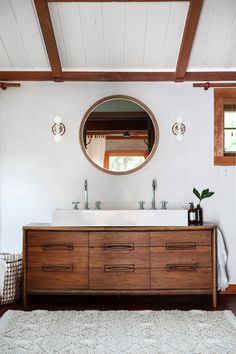bright bathroom with custom vanity and long farm sink