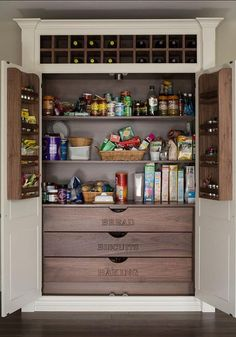 Double doors lined with spice shelves open to a kitchen pantry fitted with a stacked shelves over pull out bread, biscuits and baking drawers.