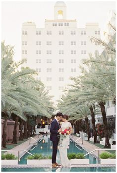Bride and groom photographed by the pool at The National Hotel in Miami Beach, FL. Bouquet by Ever After Event & Floral Design and wedding dress from Gossamer Vintage. Image by Gianny Campos Photography.