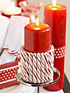 Grab your plain tall pillar candles and embellish them with some yummy candy cane sticks. Double sided tape is all that is needed to hold these on to create a very festive look.