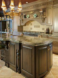 Kitchen countertops of possibly Mombasa Granite, dark brown cabinets on island, white-washed cabinets in main kitchen, island sink, interesting backsplash pattern.
