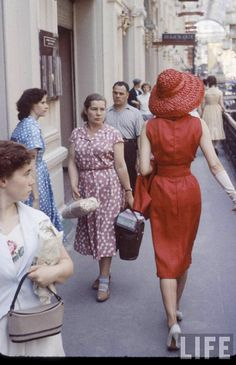 "A Christian Dior model walking through Moscow's Gosudarstvenniy Universal'niy Magazin (""State Universal Store"", or ""GUM"") attracts crowds by the contrast of her bright colors and western style in a cropped 35mm transparency photographed by Howard Sochurek for LIFE Magazine (1954)."