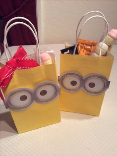 Despicable Me Minion gift bags, I used the minion mask favors from party city on yellow craft bags and then filled them with goodies such as General Mills minion fruit snacks and Nabisco minion mini cheese nips, marshmallow cupcake treats minion masks and party favors, red bows for the girls attending the party