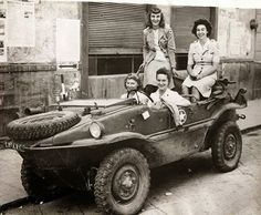 3 members of the American Red Cross in a 'stolen' Schimmwagen. The Americans took it when the Germans left it behind.