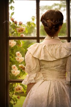 woman in Victorian dress looking out of a windowBY: Lee Avison