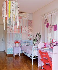 Desenhos, enfeites e estampas contam a história de Maria, dona deste quarto de 20 m². Na parede da cabeceira, sua mãe optou por usar um papel de parede estampado que parece um patchwork de tecidos em tons pastel