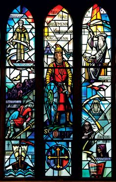 """The stained glass in Boe Chapel includes this panel that symbolizes the spread of Christianity into northern Europe. At center is Norway's King Olaf II Haraldsson (at center) and his cry, """"Fram, Fram, Kristmenn, Krossmenn, Kongsmenn"""" (""""Forward, Onward, Men of Christ, Men of the Cross, Men of the King""""). The window also depicts Olaf's death at the Battle of Stiklestad (in 1030) and Leif Erickson's voyage to America."""