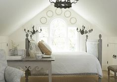 Rustic/elegant white attic bedroom - plates on the walls, sconces, chandelier - Jackye Lanham