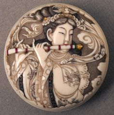 Ivory Manju netsuke depicting a woman playing a flute. Coloured decoration on the flute, head-dress and sleeves.