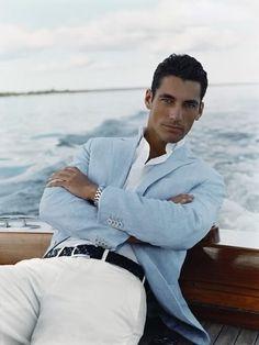Model David Gandy. Summer Chic. Dark haired man on a boat. Blue blazer, white pants.