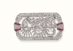 RUBY AND DIAMOND BROOCH   Designed as an old European and rose-cut diamond rectangular open plaque, with pierced corners and calibré-cut ruby detail, the inside with diamond-set stylised feathers, enhanced by marquise-cut and collet diamonds to the central heart-shaped diamond