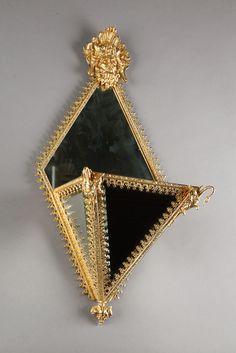 Originale jardinière suspendue en bronze doré et ciselé, comportant sur toutes ses bordures une frise ajourée de style néogothique. Le réceptacle de forme pyramidale est recouvert sur ses trois faces de miroirs et est orné aux angles d'un cygne. Le sommet de la partie murale est décoré d'un mascaron comportant une couronne de palmettes. Les miroirs d'origine sont tous biseautés.Circa : 1840Dim: L:36cm, P:24cm, H:74cm. #art #gallery