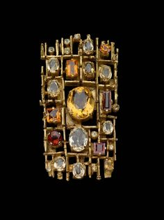 The brooch consists of a rectangular grid set with oval and fancy-cut yellow, orange, and colorless topaz within boxed surrounds. Weight: 29.1 dwt.