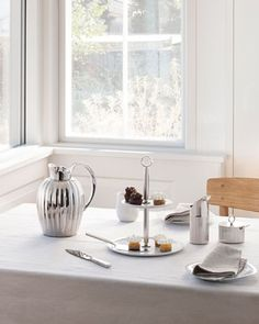 Bring a touch of timeless elegance to your table with the Bernadotte collection.  Bright Scandinavian Home with the table set for tea. Click to see this stunning collection!  #GeorgJensen #GeorgJensenBernadotte #BernadotteCollection #Craftsmanship #SigvardBernadotte