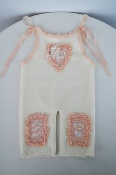 Adorable newborn girl romper, made of cream, soft, stretchy knit fabric. It has on knees ruffle lace patches, in soft coral pink color and