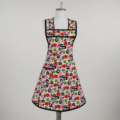 Make everyday fun in this vibrant retro apron covered with bold and beautiful pop culture flowers--sure to add pizazz to your next foray into the kitchen!    This feminine and flirty pinafore style apron is traditional in design, with thouroughly modern appeal. Bright, pretty, funky florals in lime green, fushia, red, black, and orange on a white background--not to mention a few little lady bugs also making an appearance. The apron skirt and bodice are cut on the bias to give a flattering…
