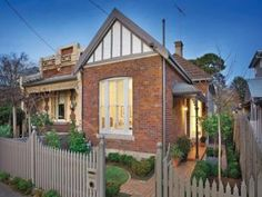 Brick victorian house exterior with picket fence & hedging - House Facade photo 525409