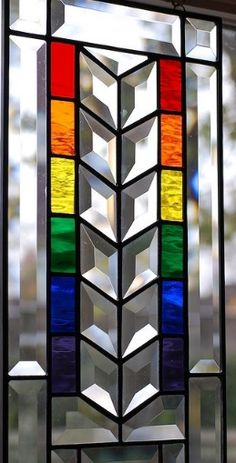 I like the beveled glass detail in the central panel but i would probably use dimpled glass as contrast in the surrounding setting (different dimple grade to the rainbow sections) or that smokey swirly glass.