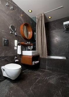 The Visaya, Delhi- Dark grey and wood is an unusual though interesting combination for the bathroom.
