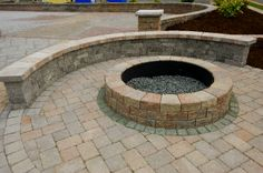 Unilock Round fire pit with a Brussels seating wall. Great addition to any patio!