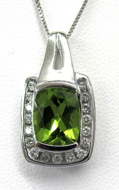 Ladies 14kt white gold gemstone and diamond pendant. Mounted in pendant is a oval cut peridot and 17 brilliant round cut diamonds weighing approximately .25ct. Pendant comes with a 18 inch white gold chain.
