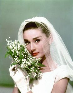 Audrey Hepburn holding a bouquet of Lily of the Valley flowers for the movie Funny Face, 1956.