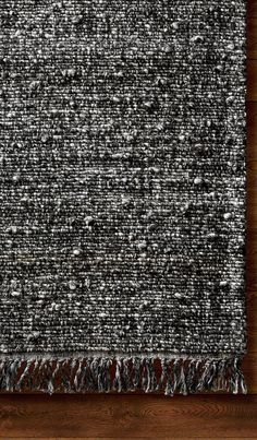 A combination of colors comes together to create an alluring all-over texture inspired by tweed fabric. Wool and polyester are handwoven to create a flatweave rug with a luxurious feel that will last for years.