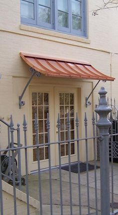 Concave copper awning with supports- simple and clean.