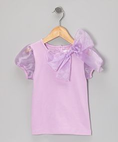 Glamour doesn't have to wait for special occasions. This gorgeous top is as comfy as a casual tee, but with the added beauty of a big fanciful bow and adorable puffy sleeves, it creates a look that's darling any day of the week. Size note: This item runs small. Please refer to the size chart when ordering.