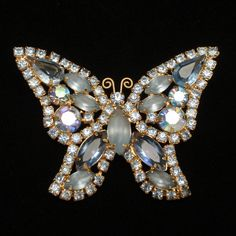 """Pretty butterfly with sparkly blue rhinestones set in silver tone metal. This butterfly pin is in good to very good condition. It is hallmarked Weiss on the reverse. The butterfly measures 1 3/8"""" x 2"""""""