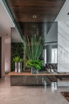 design goals - Upon entering this home, there is greenery everywhere, like the green walls and this arrangement positioned in front of a mirror.