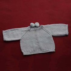 Abriguito de punto de perlé con pompones, para bebé. Trasera.