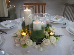 trio of pillar candles in vases wrapped in green ti leaves with hydrangeas, peonies, and roses around the outside surrounded by votives.