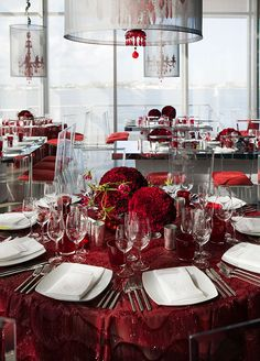 Two carnation pomanders are sitting on matching red linens for a beautiful centerpiece.