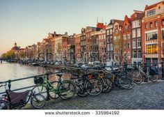 Beautiful tranquil scene of the city of Amsterdam. Bicycles along the street on the bridge over the canal. - stock photo