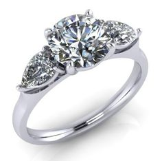 Three stone engagement ring with a centre round diamond and two pear shape diamonds