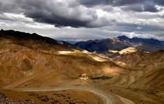 Shades: The Ladakh range near Lamayuru, Ladakh, Jammu and Kashmir. The colors of these ranges keep on changing as the day progresses. The blue shades of the mountains enveloped by clouds afar added to the natural contrast with the golden hue of sun in front.
