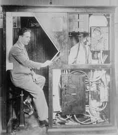 A photograph of Anatol Josepho pictured sitting inside the  Photomaton, the automatic photo booth he invented in 1925