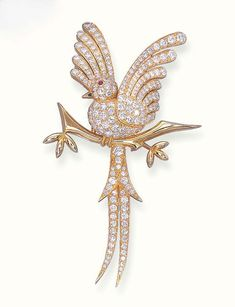 A DIAMOND BIRD OF PARADISE BROOCH, BY VAN CLEEF ARPELS With raised wings, the bird set with circular-cut diamonds to the cabochon ruby eye, perched on a gold branch, mounted in 18k gold
