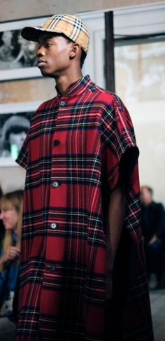 A Modern Stewart Royal tartan poncho insulated in double-faced wool cashmere, worn with a Vintage check baseball cap on the September 2017 runway.