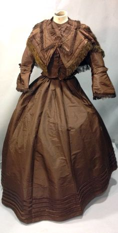 Afternoon dress and matching stole ca. 1860. Glossy brown silk faille with silk satin  pleats and fringe. Short bodice, boned and buttoned; pagoda sleeves, buckram lining. Pleated skirt. Thierry de Maigret
