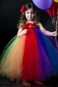 This beautiful and fun tutu dress has all of the colors of the rainbow! Accented by 3 pretty red flowers and satin straps that tie in two bows at the back. This could be made with more muted colors and different kinds of flowers across top