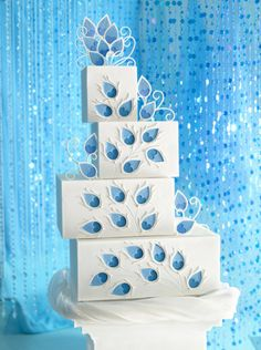 "cake ... mod look ... square layers stacked off center ... white fondant frosting ... blue paisley feather  shapes ... I'm thinking ""peacock"", but probably not ... fun cake!! ... this was a suggestion for a wedding cake for William and Kate: Something Blue ..."
