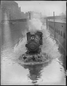 Steam locomotive showing its teeth going through the rough flood cause by the heaviest rain of the season  Boston 1915 photo by Leslie Jones