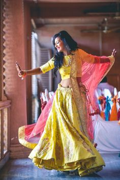 Happy dancing bride in yellow lehenga