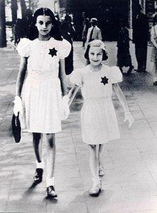 ><  Belgium,                        two girls in white with dark Jewish stars,                        Keizerlei, Antwerpen 1942
